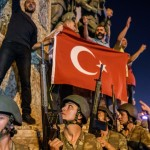 TOPSHOT - Turkish solders stay with weapons at Taksim square as people protest agaist the military coup in Istanbul on July 16, 2016.  Turkish military forces on July 16 opened fire on crowds gathered in Istanbul following a coup attempt, causing casualties, an AFP photographer said. The soldiers opened fire on grounds around the first bridge across the Bosphorus dividing Europe and Asia, said the photographer, who saw wounded people being taken to ambulances.   / AFP / OZAN KOSE